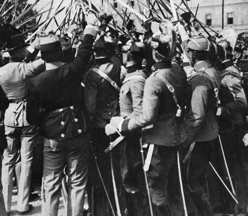 Oficerowie monarchii austro-węgierskiej manifestują na ulicach Wiednia gotowość do walki za ojczyznę i najjaśniejszego pana. Wykwintne, paradne mundury różnych formacji i wzniesione w górę szpady i szable symbolizują poczucie siły i jedności elity cesarsko-królewskiej armii. Iluż oficerów, demonstrujących latem 1914 r. pewność siebie i optymizm, mogło przypuszczać, że nieco ponad cztery lata później tron, któremu ślubowali wierność - runie, a państwo, którego mieli bronić i dla którego mieli zwyciężać - całkowicie się rozpadnie?
