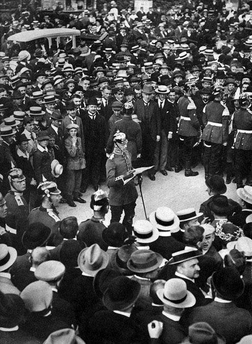 Główna aleja Berlina Unter den Linden w dniu 31 lipca 1914 r. Niemiecki oficer odczytuje zgromadzonym tłumom cesarski akt o stanie bezpośredniego zagrożenia wojną. Oznaczało to postawienie w stan alarmu zgromadzonych na granicach wojsk. Berlińczyków ogarnął bezprecedensowy entuzjazm. Powszechnie uznano wybuch wojny za przesądzony, a radość z tego powodu kazała Niemcom w wielu miastach hucznie świętować przez kilka najbliższych dni i nocy. Prawdziwa euforia ogarnęła poddanych Wilhelma II, gdy jego ambasadorowie wypowiedzieli wojnę Rosji (1 sierpnia) i Francji (3 sierpnia).