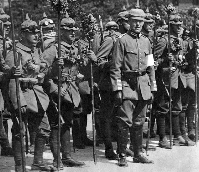 Niemieccy ochotnicy pod dowództwem sędziwego weterana. Oprócz takich atrybutów, związanych z radością z powodu wybuchu wojny, jak kwiaty, którymi udekorowani są żołnierze, wiele mówią twarze sfotografowanych chłopców. Bardzo młode, myślące, inteligentne. Dwóch z nich nosi okulary. Być może to uczniowie lub studenci. Na początku wojny zaciągnęły się do armii dziesiątki tysięcy podobnych do nich ochotników, którzy bez trudu mogli liczyć na zwolnienie ze służby wojskowej. O przywdziewanie mundurów apelowali do swych studentów rektorzy niemieckich uczelni i przedstawiciele świata kultury. Ogół społeczeństwa ogarnął amok. Sądzono, iż wybiła godzina, w której Niemcy pokażą światu, czego są warci i na co ich stać. Wojna i przemoc, ale także i ofiara z przedstawicieli własnego społeczeństwa, miały być ceną za nową, wspaniałą przyszłość Rzeszy.