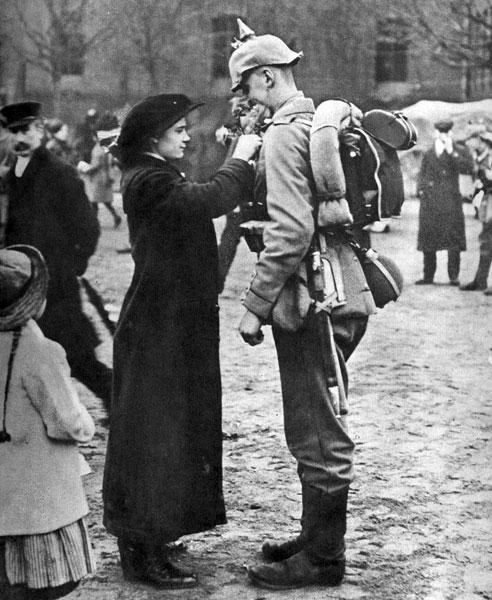Niemiecka dziewczyna żegna odchodzącego na front żołnierza. Przypinane do polowego munduru kwiaty nie uosabiały żalu czy niepokoju o los bliskich, udających się na wojnę. Oczekiwano rychłego ich powrotu w glorii chwały, jako zwycięzców. Przekonanie o nieuchronności wielkiego, czekającego Niemcy sukcesu sprawiało, że celebrowane solennie w całej Rzeszy uroczystości pożegnalne były autentycznie radosne i optymistyczne.