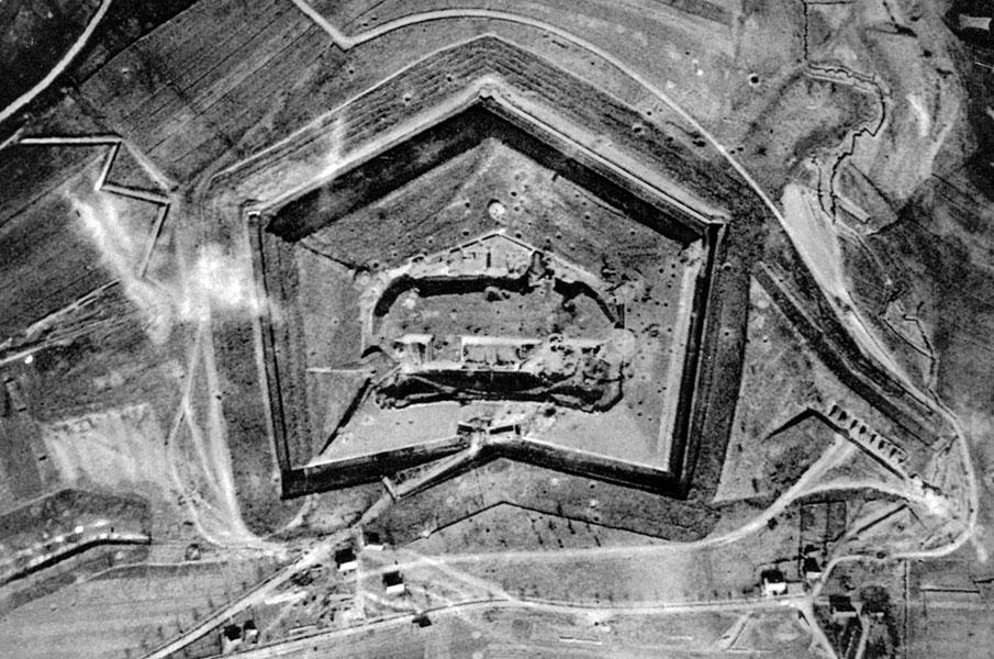 Fort Douaumont wczesną wiosną 1916 roku. Przedstawiony na zdjęciu bastion był jednym z głównych punktów obrony systemu umocnień wokół Verdun. Miasto otaczało około 30 podobnych do Douaumont fortów, samodzielne baterie artyleryjskie, zasieki, układające się w kilka linii obrony okopy. Fortyfikacje te okazały się bardzo trudne do zdobycia. Wprawdzie w pierwszych dniach ofensywy Niemcy opanowali część francuskich pozycji, jednak w marcu i kwietniu impet natarcia osłabł. Generał Joffre polecił przerzucić pod Verdun znaczne posiłki, jednocześnie dowództwo obrony rejonu Verdun powierzając generałowi Philippowi Pétain. Zaciekła obrona Francuzów osadziła w miejscu niemieckie natarcie, co zamieniło walki pod Verdun w krwawą i wycieńczającą wojnę pozycyjną.