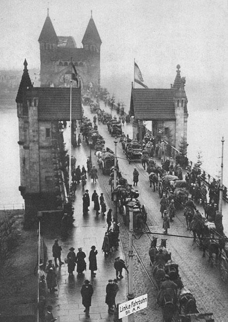 Z powrotem przez Ren... Wycofujące się z Frontu Zachodniego oddziały niemieckie na moście w Bonn. Klęska armii niemieckiej była zupełna. Porażkę odniesioną w polu przypieczętowały rozruchy rewolucyjne w głębi państwa. W początkach października szef nowego rządu, książę Maksymilian Badeński, podjął próbę wy-negocjowania z prezydentem Wilsonem korzystnych warunków rozejmu. 9 listopada abdykował cesarz Wilhelm. Funkcję kanclerza przejął socjaldemokrata Friedrich Ebert. 11 listopada 1918 roku w lasku Compiegne podpisany został rozejm. Niemcy wydawali pokaźną część swego sprzętu wojennego, wycofywali się z zajmowanych terenów Francji i Belgii, zwracali Alzację i Lotaryngię, zrzekali się posiadłości kolonialnych. Wojna była skończona.