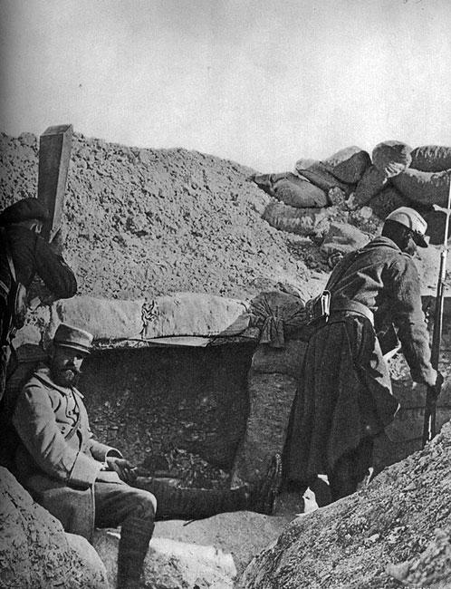 Okopy francuskie w Szampanii, początek 1915 roku. Życie wepchniętych do okopów żołnierzy upływało przede wszystkim pod znakiem nieustannego czuwania i oczekiwania na atak. Dyżurny obserwator śledzi sytuacje na przedpolu przez lornetkę peryskopową. Wartownik z nasadzonym na karabin bagnetem udaje się na swój posterunek. Okop umocniony workami z ziemią. Jak mawiali walczący, wojna się skończy, gdy zabraknie Belgii do sypania jej do worków...