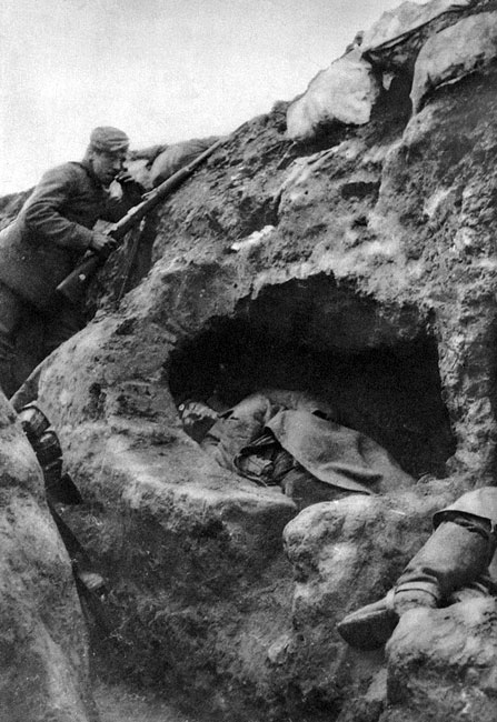 Niemcy pod Arras w 1914 roku. Nerwowo paląc papierosa, z karabinem w dłoni, stale spoglądając w kierunku pozycji przeciwnika, niemiecki żołnierz umożliwia krótki odpoczynek swym kolegom. Śpią oni w wygrzebanych we frontowej ścianie okopu 'norach tchórza', gotowi zerwać się do walki w razie ataku.