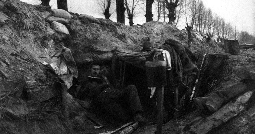 Spokojne dni na froncie. Gdy nastawał spokój, żołnierze mogli pozwolić sobie na dłuższe wytchnienie. Rozrzucone w nieładzie buty, hełm - pikielhauba, karabin, mundur, dyndająca na drewnianym drążku menażka, a zwłaszcza niedbała poza pogrążonego w lekturze żołnierza świadczą o zachłannym chwytaniu przezeń oczekiwanej chwili relaksu.