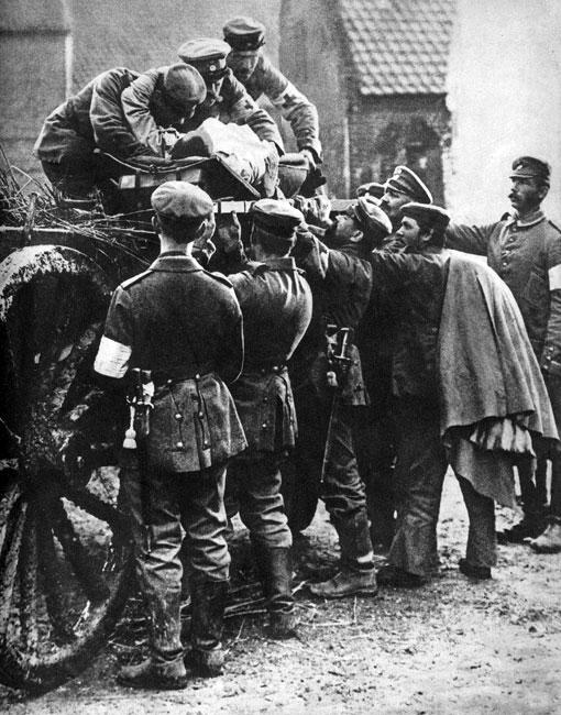 Pierwsze ofiary - niemieccy sanitariusze ewakuują rannego. W chwili wybuchu wojny nie myślano o ofiarach, które trzeba było ponieść. Żołnierze maszerujący na front nie dopuszczali do siebie myśli, że mogą zginąć. Rodziny, żegnające bliskich udających się do walki, wierzyły, że powrócą wkrótce cali i zdrowi. Jednak od pierwszych chwil wojna zbierała swe tragiczne żniwo.