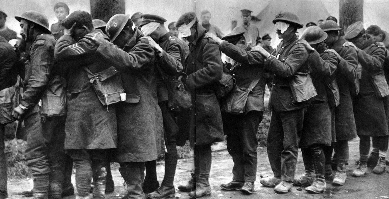 Angielscy żołnierze, oślepieni po ataku gazowym. Jedno z najbardziej znanych zdjęć Pierwszej Wojny Światowej, przedstawiające korowód ślepców. Wszyscy żołnierze mają przewieszone przez ramiona torby z maskami przeciwgazowymi. Często okazywały się one nieskuteczne - zwłaszcza wobec stosowania coraz to nowych środków chemicznych. Jeżeli nawet nie uśmiercały one zaatakowanych, to skutecznie eliminowały ich z walki, porażając najczęściej oczy. Żołnierze obu stron konfliktu nienawidzili gazu - uważali go za broń niehonorową. Paraliżowała ich bezbronność wobec potwornego zagrożenia, jakie ze sobą niósł. Ukryci w okopach, podziemnych schronach, bezpieczni od pocisków wroga - ulegali jednak dławiącym oparom, niosącym straszne męczarnie.