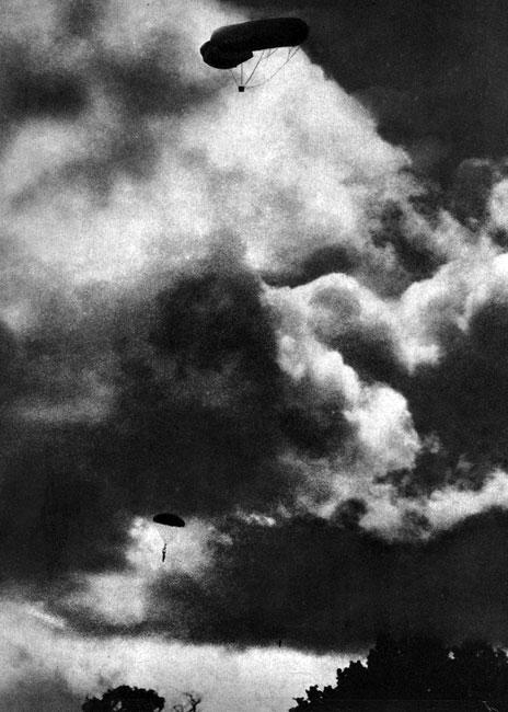 Balon na uwięzi. W czasie, gdy samoloty były jeszcze bardzo niedoskonałe, a warunki wojny pozycyjnej wymagały dokładnej obserwacji stanowisk przeciwnika, do zwiadu powietrznego z powodzeniem używano balonów. Zakotwiczone na ziemi, mogły - nawet podczas silnego wiatru - zachować swą pozycję, co umożliwiało załodze śledzenie działań nieprzyjaciela i obserwowanie skuteczności własnej artylerii. Balony były jednak łatwym celem dla wrogich samolotów. Być może przedstawiony na fotografii skoczek spadochronowy salwuje się ucieczką zagrożony właśnie przez obcego pilota.