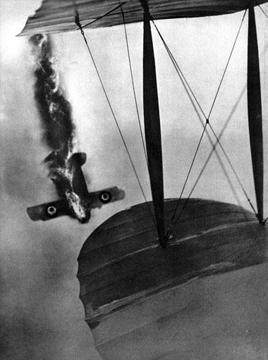 Zestrzelony angielski samolot sfotografowany z pokładu niemieckiego aeroplanu. Walki powietrzne staczano już na samym początku konfliktu. Wykorzystywano przy tym karabin maszynowy obsługiwany przez drugiego członka załogi - czyli obserwatora. Kolejne lata wojny przyniosły znaczny postęp w dziedzinie powietrznych pojedynków. Przełomowe znaczenie miało skonstruowanie wiosną 1915 roku przez francuskich inżynierów śmigieł zaopatrzonych w specjalne wzmocnienia chroniące przed pociskami karabinowymi. Umożliwiło to zamontowanie karabinu maszynowego przed kabiną pilota tak, by mógł on samodzielnie prowadzić ogień do samolotów przeciwnika. Wybitny francuski lotnik Roland Garros, który jako pierwszy zaopatrzył swą maszynę w nowy wynalazek, w ciągu dwóch tygodni strącił sześć niemieckich samolotów, których załogi nie spodziewały się niebezpieczeństwa ze strony małego, jednoosobowego aeroplanu.