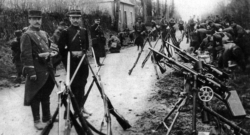 Oddział francuskiej piechoty w drodze na front w sierpniu 1914 roku. Żołnierze odpoczywają w przydrożnych rowach. Oficer pozuje do zdjęcia stojąc obok dwóch karabinów maszynowych Hotchkiss. Strategia armii francuskiej na wypadek konfliktu z Niemcami była strategią zdecydowanie ofensywną, zakładającą atak na tereny Alzacji i Lotaryngii. Do planów sztabowców dostosowane zostało uzbrojenie armii. Posiadanie przez wojska III Republiki karabinów maszynowych wynikało z przeświadczenia o ich przydatności jako broni nadającej się przede wszystkim do ataku. Pierwsze tygodnie walk miały jednak przynieść doświadczenie, że karabin maszynowy jest absolutnie nieodzowny w działaniach obronnych. Wojna pozycyjna utrwaliła to przekonanie. Karabiny maszynowe stały się podstawowym elementem wyposażenia walczących armii. Hotchkiss należał do jednych z najbardziej udanych i najpopularniejszych konstrukcji. W czasie Wielkiej Wojny używały go armie alianckie. Po wojnie eksportowany był przez Francje do wielu państw. W Wojsku Polskim mówiono o nim, trawestując znaną łacińską maksymę, Nec Hercules contra Hotchkiss (Nawet Herkules nie da rady Hotchkissowi).
