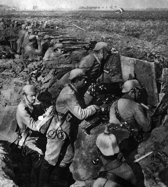 Niemiecki karabin maszynowy na stanowisku ogniowym. Obsługę jednego karabinu maszynowego stanowiło, w zależności od typu, kilku żołnierzy. Na zdjęciu widzimy: dowódcę - lustrującego przez lornetkę przedpole i kierującego ogniem, celowniczego - prowadzącego ostrzał oraz, po prawej - amunicyjnego, podającego taśmę z nabojami ze specjalnej skrzynki do komory nabojowej. Ponadto w okopie znajduje się jeszcze dwóch żołnierzy, którzy (podobnie jak obsługa) zaopatrzeni są w szerokie skórzane pasy ze specjalnymi uchwytami do przenoszenia 'kaemu'. Była to broń niesłychanie skuteczna. W ciągu minuty wystrzeliwała do 500 pocisków, skutecznie rażących przeciwnika znajdującego się w odległości nawet 2,5 kilometra. O jej celności decydowało zaopatrzenie w masywne, pozwalające utrzymać stateczność podstawy i precyzyjne mechanizmy celownicze.
