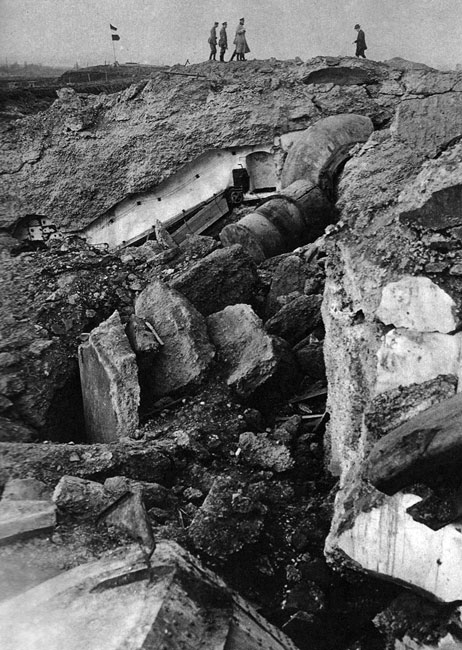 Potworne skutki ognia 'Grubej Berty'. Niemieckie oddziały generałów Ludendorfa i von Emmicha zajęły belgijskie Liége już 7 sierpnia 1914 roku. Dwanaście, rozrzuconych wokół miasta, fortów uniemożliwiało jednak dalszy marsz na zachód i opóźniało niemiecką ofensywę. 'Forty trzymają się nadal' - donosiły gazety. Bohaterska postawa dowodzonych przez generała Lemana żołnierzy dodawała otuchy całej Belgii. Aby pokonać obrońców postanowiono ściągnąć pod Liége najcięższą artylerię. Dwie 'Grube Berty' przetransportowano koleją 10 sierpnia. Wobec zniszczenia przez Belgów linii kolejowych, ostatni odcinek drogi moździerze musiały pokonać o własnych siłach. Ze względu na ciągłe defekty ciągników, przebycie 18 kilometrów zajęło cały dzień. 12 sierpnia rozpoczęto bombardowanie belgijskich umocnień. Ogromna siła rażenia obracała żelbetonowe fortyfikacje w ruinę. Obrońców, biernie oczekujących na śmiercionośne salwy, paraliżował przerażający strach. Pociski, zaopatrzone w zapalniki z opóźnionym zapłonem, eksplodowały dopiero po przebiciu wielometrowych stropów fortyfikacji... 16 sierpnia opór Belgów został złamany. Kilka dni później podobnie potoczyły się losy umocnień wokół Namur.