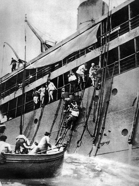 Transportowiec francuski 'Santay' storpedowany na Morzu Śródziemnym. Załoga opuszcza pokład statku, znajdując schronienie w szalupach ratunkowych. Celem ataków U-bootów padały nie tylko alianckie okręty wojenne, ale także statki handlowe. Warunki prowadzenia wojny na morzach określone były przez konwencje haskie z 1899 i 1907 roku. Dopuszczały ona atakowanie jednostek handlowych, po ich uprzednim uprzedzeniu i umożliwieniu załodze ewakuacji (tzw. prawo pryzowe). Do początku 1915 roku Niemcy przestrzegali norm międzynarodowych.