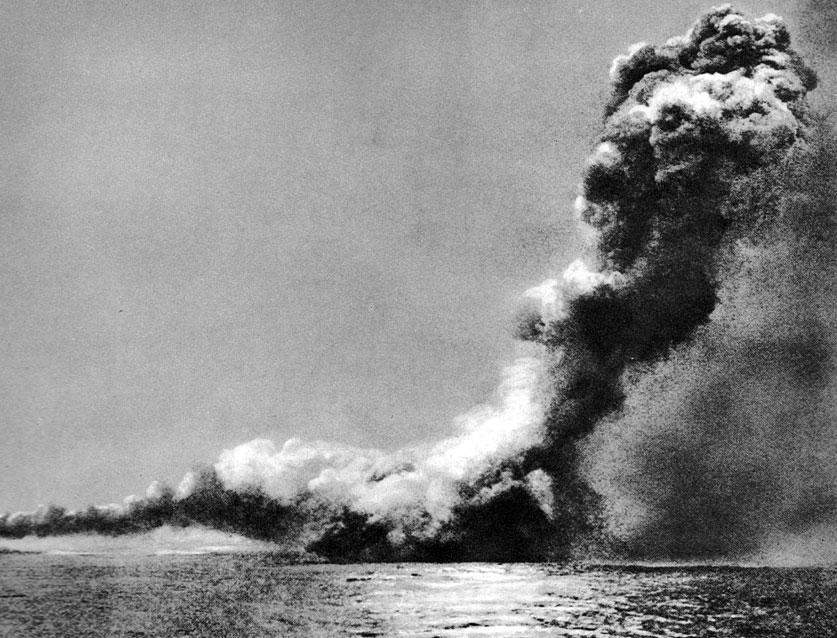 Eksplozja na krążowniku 'Queen Mary'. Zdjęcie przedstawia spowity chmurą dymu okręt. Wziął on udział tylko w pierwszej fazie bitwy w Skagerrak. Celnym ogniem artyleryjskim zadał ciężkie straty krążownikowi 'Seydlitz'. Odpowiedź jednostki niemieckiej była jednak straszna w skutkach. Salwa 'Seydlitza' spowodowała wybuch amunicji i błyskawiczne zatonięcie