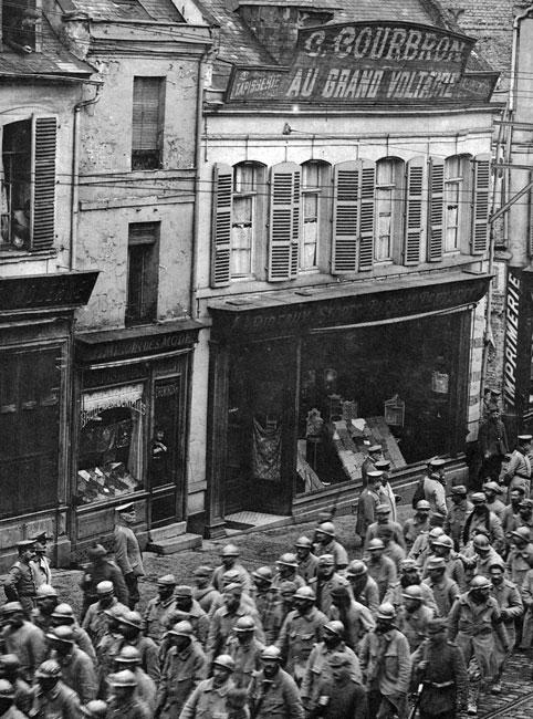 Kolumna francuskich jeńców na ulicach Saint-Quentin wiosną 1918 roku. Ogromne ilości żołnierzy dostawały się do niewoli nawet w ostatnich miesiącach walk. W wyniku podjętej 21 marca 1918 roku ofensywy na Froncie Zachodnim, w okolicach Saint-Quentin, Niemcy wzięli 90 tysięcy jeńców. Długie kolumny ciągnęły na zachód ulicami francuskich miast, mając przypominać ich mieszkańcom, że losy wojny jeszcze się ostatecznie nie rozstrzygnęły. Zwracają uwagę puste okna i obecność jedynie samych Niemców na ulicach - tak, jakby Francuzi nie chcieli w żaden sposób, nawet jako widzowie, uczestniczyć w tej upokarzającej manifestacji.