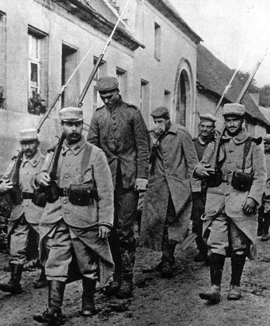 Wielkolud. Niekiedy trafienie do niewoli wiązało się z nieco humorystycznymi okolicznościami. Niemiecki żołnierz o zaiste imponującym wzroście prowadzony pod silną eskortą francuską. Strażnicy, szczęśliwi i uśmiechnięci, nie kryją zadowolenia. Na wszelki wypadek trzymają jednak w pogotowiu karabiny z nasadzonymi na nie bagnetami.