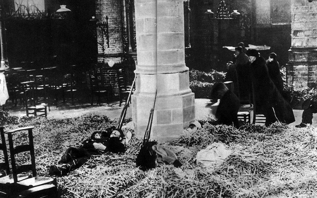 Stara i nowa funkcja kościoła. Znużeni belgijscy żołnierze śpią na sianie rozrzuconym na kościelnej posadzce. Cywile, tuż obok nich, modlą się przed ołtarzem. W nowych realiach padały świętości. Konflikt, w którym Niemcy dążyli do uzyskania globalnej dominacji, a alianci bronili dawnego układu sił, odmienił również dotychczasowe wartości i normy. Zdumienie świata wzbudził już sam początek walk. Ofiarą oszalałego bestialstwa padła Belgia. Zgwałcono jej neutralność. Niemieccy najeźdźcy popełniali masowe zbrodnie na ludności cywilnej. Spalili historyczne Louvain, nie oszczędzając unikalnej, średniowiecznej biblioteki.