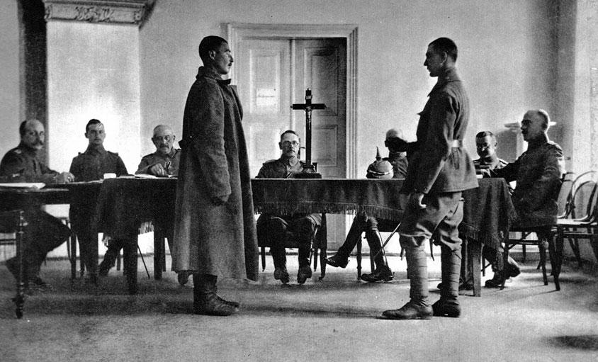 Rosyjski szpieg przed niemieckim sądem wojskowym. Jedną z cech Wielkiej Wojny jako wojny totalnej było uruchomienie przez walczące strony gigantycznego aparatu propagandowego. 'Wojna psychologiczna', jak ją nazwał prof. Jerzy Holzer, służyć miała podtrzymaniu morale żołnierzy i obywateli oraz zohydzeniu, w oczach własnego społeczeństwa, wizerunku przeciwnika. Nękano również bezpośrednio wrogów, chcąc osłabić ich wolę walki. Poważnym problemem było wyjaśnienie obywatelom przyczyn przedłużania się konfliktu i ponoszenia klęsk. Stąd też jednym z motywów, powracających w propagandzie wojennej, była sugestia, jakoby szczególną aktywność rozwijali spiskowcy i tajni agenci. Jakie rozmiary przybierało polowanie na szpiegów, łatwo uzmysłowić sobie na podstawie losów Dobrego Wojaka Szwejka z powieści Jaroslava Haszka. W okresie międzywojennym zakorzenione dość powszechnie przeświadczenie o istnieniu rzekomego, tajemnego porozumienia wrogich sił ułatwiało manipulowanie nastrojami społeczeństw. Wynajdywanie wspólnego wroga legło u genezy ruchów totalitarnych. Zwłaszcza Niemcy, nie mogący się pogodzić ze skutkami wojny, przyjęli nazistowską tezę o ciosie wymierzonym w plecy.