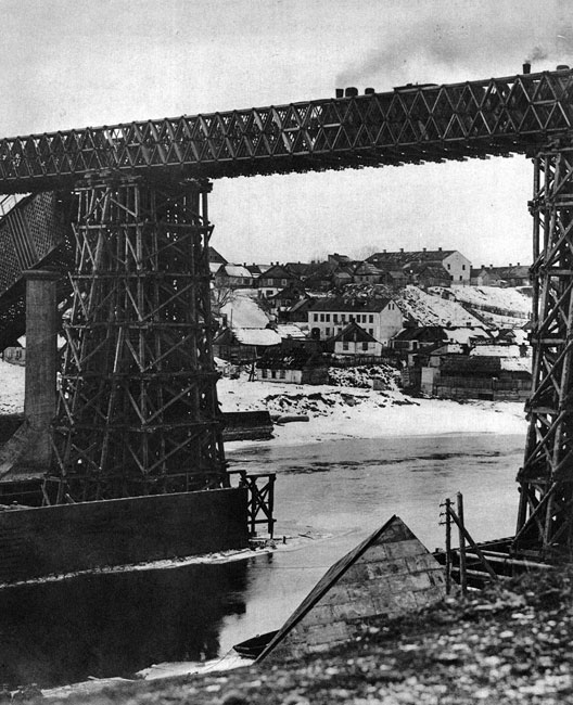 Most na Niemnie w Grodnie. Wojska rosyjskie, wycofujące się pod naporem ofensywy państw centralnych w 1915 roku, za wszelką cenę starały się opóźnić pochód nacierających armii. Niszczono tory kolejowe, wysadzano w powietrze mosty. Utrudniało to marsz Niemców i Austriaków, zmuszając jednocześnie do konstruowania prowizorycznych przepraw, jak choćby przedstawiony na zdjęciu drewniany most kolejowy w Grodnie. Konstrukcje niemieckich saperów były jednak tymczasowe, toteż zniszczenia dokonywane przez Rosjan stanowiły ostatnią, szczególnie uciążliwą pamiątkę ich rządów w Europie Środkowej.