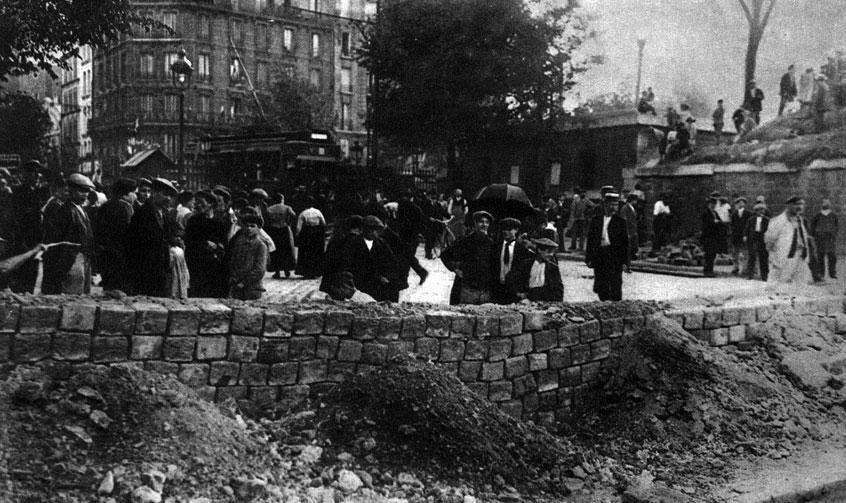 Fortyfikowanie Paryża. Barykada uliczna z kostki brukowej na przedmieściu stolicy Francji. Gdy w sierpniu 1914 roku Niemcy zbliżali się do Paryża, jego mieszkańcy spontaniczne pomagali w działaniach mających służyć obronie swego miasta. Wojna, prowadzona przeciwko całym narodom, mobilizowała całe narody. Z cza-sem same rządy zaczęły traktować obywateli jak ludzi, którzy winni podporządkować się ścisłej dyscyplinie.