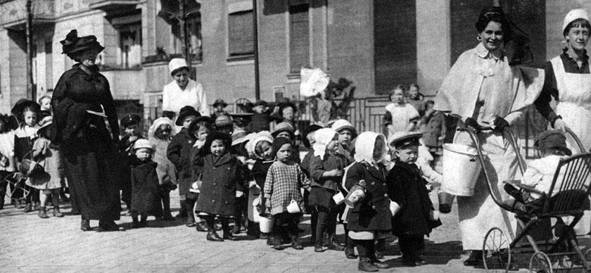 Dzieci z ochronki pod okiem swych opiekunek. W sytuacji, gdy ojcowie odeszli na front, a matki i starsze siostry pracowały, dzieci musiały znajdywać opiekę poza domem. Wychowanie przedszkolne, nie mówiąc już o żłobkach, nie było przed wojną zjawiskiem częstym. Nowe warunki egzystencji podczas wojny zmuszały coraz więcej kobiet do korzystania z tej formy opieki nad dziećmi. Umożliwiało to funkcjonowanie społeczeństwa w warunkach wojennych, prowadziło jednak do zmian w dotychczasowej obyczajowości, zwłaszcza w dziedzinie stosunków rodzinnych. Z wolna zanikał model patriarchalny, w którym ojciec zapewniał byt, a matka strzegła domowego ogniska.